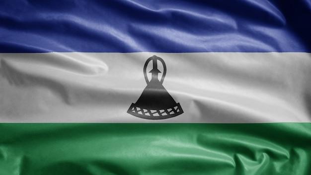 Lesotho-flagge weht im wind. nahaufnahme von sesotho banner weht, weiche und glatte seide. stoff textur fähnrich hintergrund.