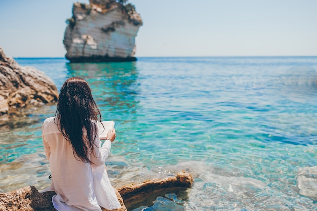 Lesung der jungen frau auf tropischem weißem strand