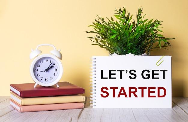 Let is get started steht in einem notizbuch neben einer grünen pflanze und einem weißen wecker, der auf bunten tagebüchern steht