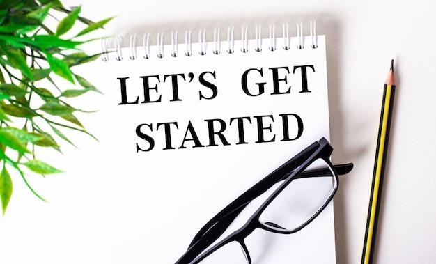 Let is get started steht in einem weißen notizbuch neben einem bleistift, einer schwarz gerahmten brille und einer grünen pflanze.