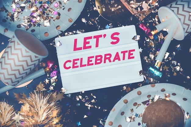 Lets feiern auf lichtkasten mit party cup, partygebläse, lametta, konfetti