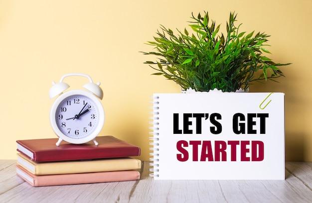 Lets get started steht in einem notizbuch neben einer grünen pflanze und einem weißen wecker, der auf bunten tagebüchern steht.