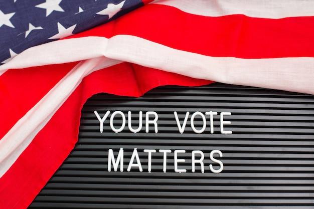 Letterboard-zeichen mit den worten ihre abstimmungsfragen mit amerikanischer flagge. us-wahlen.