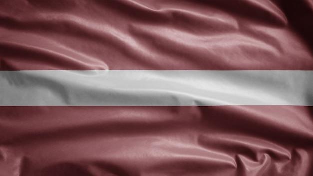 Lettische flagge weht im wind. nahaufnahme von lettland banner weht, weiche und glatte seide. stoff textur fähnrich hintergrund. verwenden sie es für das konzept für nationalfeiertage und länderanlässe.