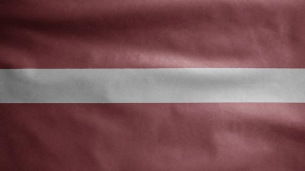 Lettische flagge weht im wind. nahaufnahme von lettland banner weht, weiche und glatte seide. stoff textur fähnrich hintergrund.