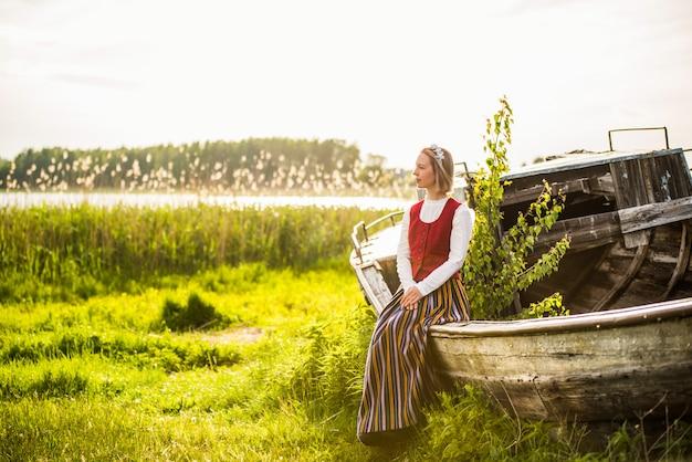 Lettische frau in traditioneller kleidung auf altem boot.