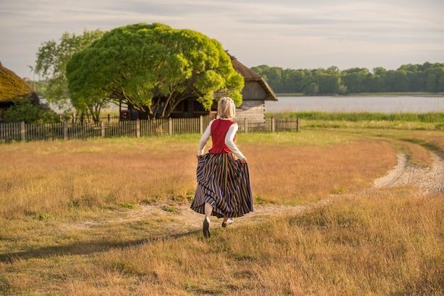 Lettische frau in traditioneller kleidung im feld.