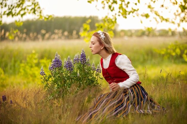 Lettische frau in traditioneller kleidung im feld
