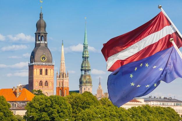Lettische und europena-flaggen mit riga-stadtbild auf hintergrund