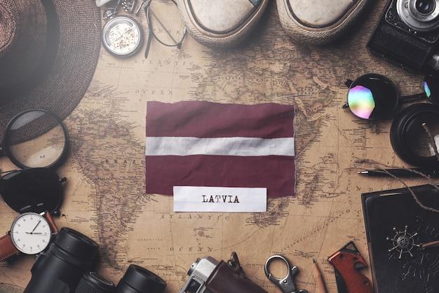 Lettland-flagge zwischen dem zubehör des reisenden auf alter weinlese-karte. obenliegender schuss