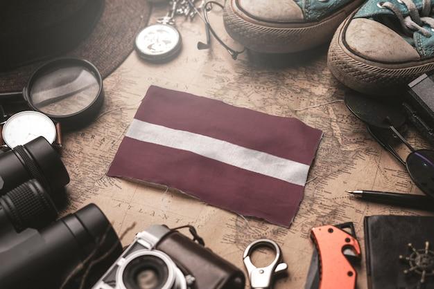 Lettland-flagge zwischen dem zubehör des reisenden auf alter weinlese-karte. touristisches bestimmungsort-konzept.