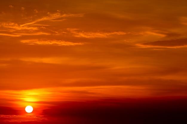 Letzter heller sonnenuntergang auf dem roten wolkenhimmelstrahl um sonne