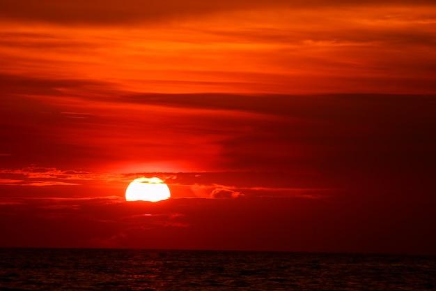 Letzter heller sonnenuntergang auf orange wolkenstrahl des himmels um sonne über meer