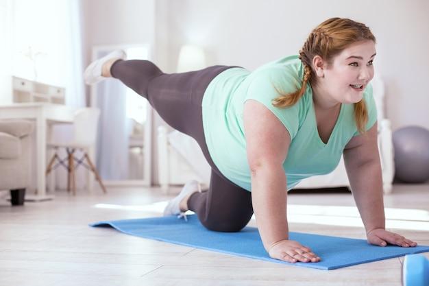 Letzter. übergewichtige junge frau, die mit den letzten übungen kämpft, während sie auf allen vieren steht