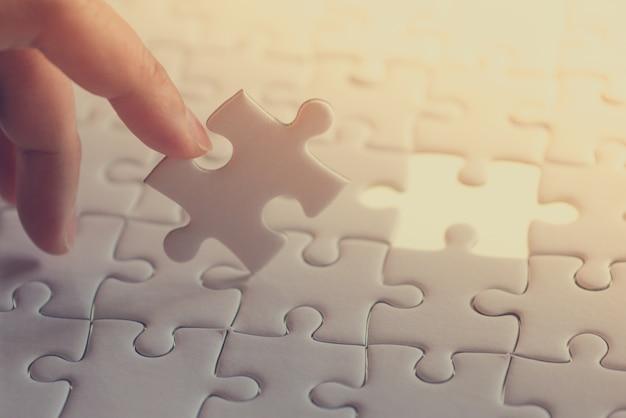 Letztes stück des puzzles, das durch zeigefinger gehalten wird