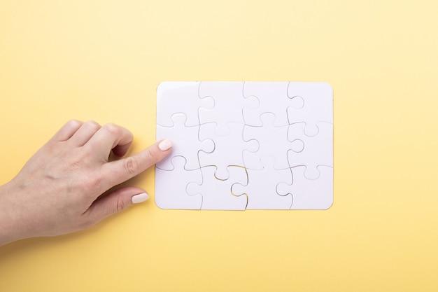 Letztes stück puzzle in der hand weißes puzzle