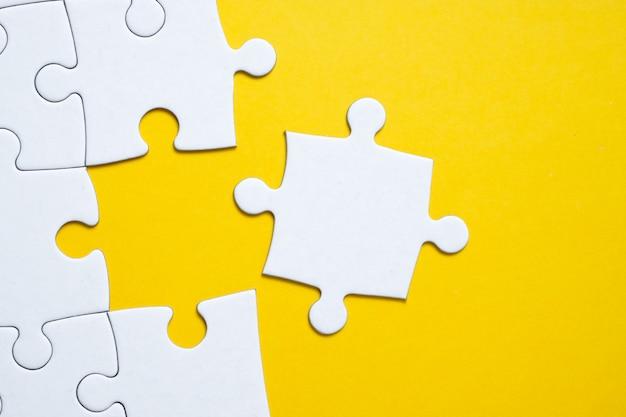 Letztes weißes stück liegt neben dem puzzle auf gelb.