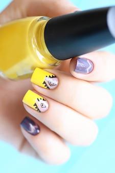 Leuchtend gelbe und violette frauenmaniküre mit null-kunst. schwarze ethnische verzierung. transparentes design. glänzende nägel.