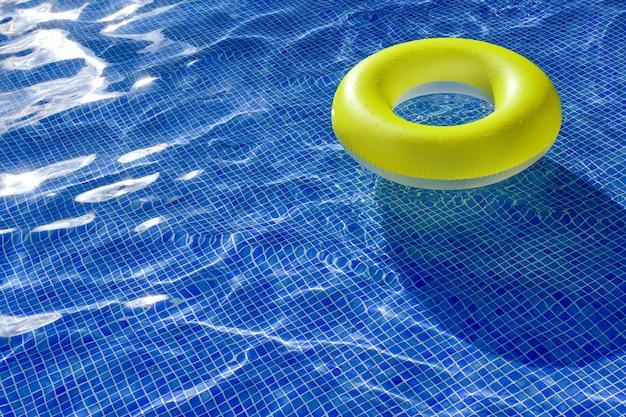 Leuchtend gelber aufblasbarer rettungsring in einem außenpool
