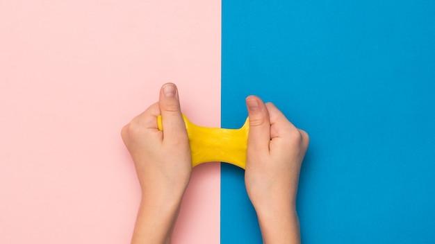 Leuchtend gelber kalk streckte sich in den händen auf einem rosa und blauen hintergrund aus. spielzeug gegen stress. spielzeug zur entwicklung der handmotorik.