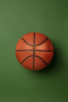 Leuchtend orange-brauner basketballball. professionelle sportausrüstung isoliert auf grüner oberfläche. konzept von sport, aktivität, bewegung, gesunde lebensweise, wohlbefinden. moderne farben.