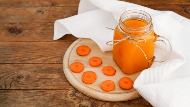 Leuchtend orange karottensaft in einem glas auf einem hölzernen hintergrund. saft und gehackte karotten. hausgemachtes getränk mit vitaminen