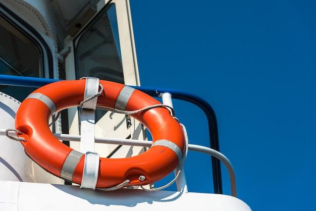 Leuchtend orange rettungsring auf einer weißen yacht
