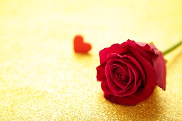 Leuchtend rote rose und herzen auf goldglitter
