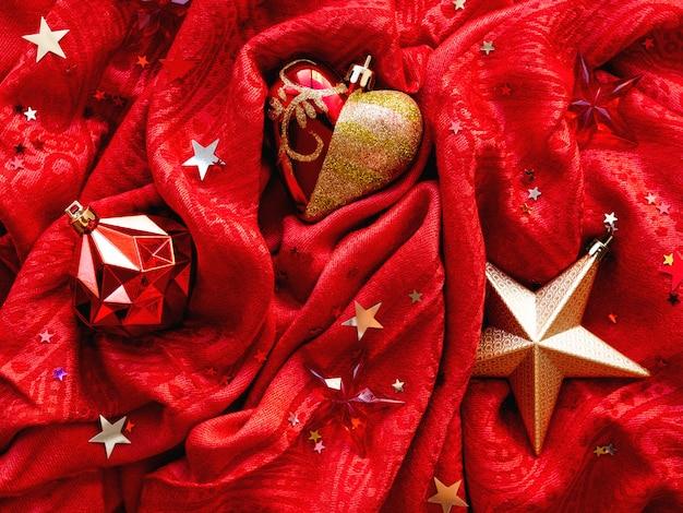 Leuchtend roter stoff mit weihnachts- und neujahrsdekorationen, goldenem stern, herz und ball. sternkonfettis auf gefaltetem textilhintergrund.