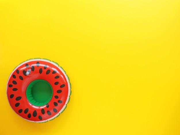 Leuchtend roter und grüner pool schweben in form einer wassermelone auf gelber oberfläche