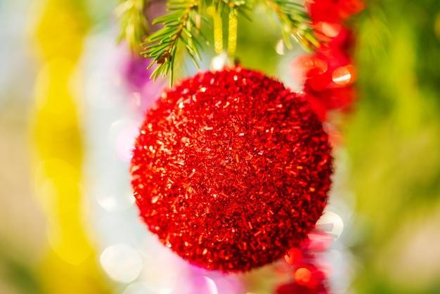 Leuchtend roter weihnachtsball und glänzender lametta, der am ast des baumes hängt. nahaufnahme des schönen weihnachtskreativkonzepts für ein glückliches neues jahr. selektiver fokus im vordergrund, verschwommenes bokeh im hintergrund.