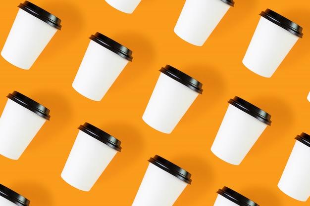 Leuchtend wirkungsvoll aus weißen pappbechern mit schwarzen deckeln auf sattem orange.