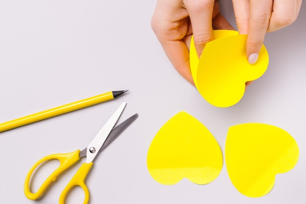 Leuchtende aufkleber in form von herzen, weiblichen händen, bleistift und schere. vorbereitung auf den valentinstag.