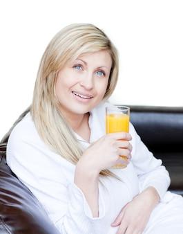 Leuchtende frau, die einen orange jus trinkt