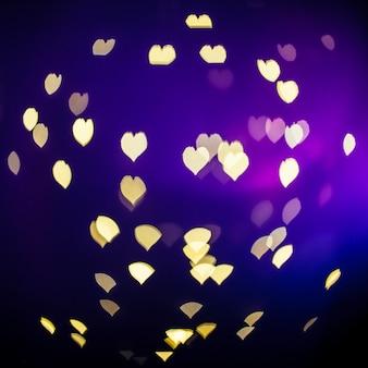 Leuchtende Herzen auf violettem Hintergrund