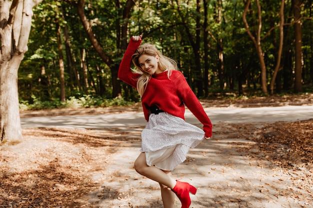 Leuchtende junge frau, die auf der sonne im park tanzt. hübsche blondine, die glücklich draußen lächelt.