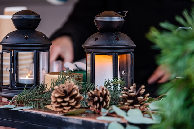 Leuchtende kerzenlaterne und weihnachtsdekorationen auf dem tisch im weihnachtsmarkt in riga, lettland