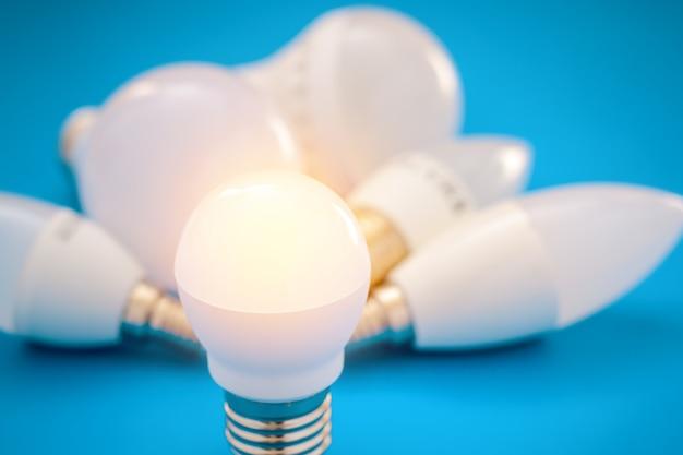 Leuchtende led-lampe in der nähe einer reihe anderer glühlampen