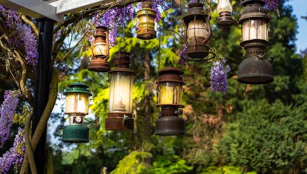 Leuchtende romantische kerzenlaternen, die in vintage-gartenlampen in der natur hängen, stilvolle antike dekoration mit bunter blumenschönheit