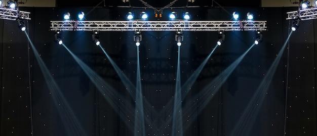 Leuchtende strahlen von der konzertbeleuchtung gegen einen dunklen hintergrund, musikinstrumentkonzept