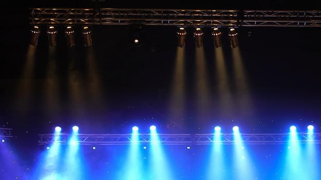Leuchtende strahlen von der konzertbeleuchtung gegen einen dunklen hintergrund