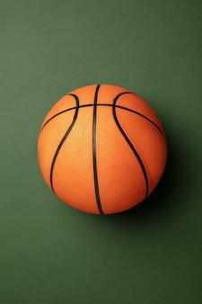 Leuchtender orange-brauner basketballball. professionelle sportausrüstung lokalisiert auf grünem hintergrund.