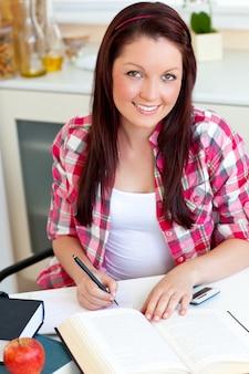 Leuchtender student, der zu hause ihre hausarbeit tut