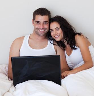 Leuchtendes paar unter verwendung eines laptops im schlafzimmer