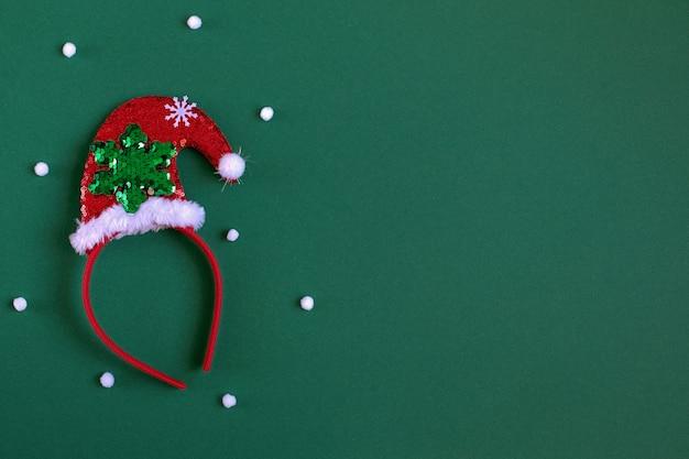 Leuchtendes randrot in form einer weihnachtsmütze auf dunkelgrünem hintergrund silvester-accessoire