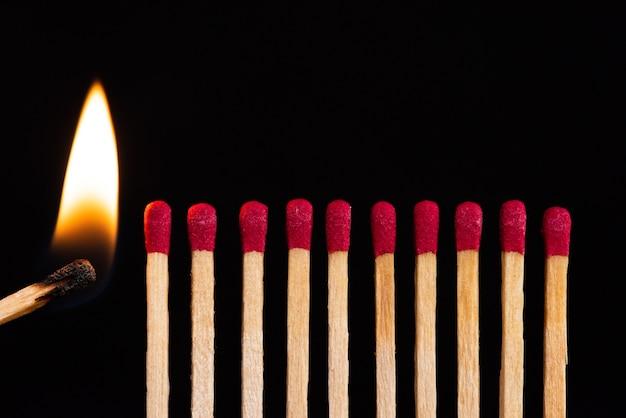 Leuchtet das spiel neben einer reihe unbeleuchteter matches. die leidenschaft des einen entzündet neue ideen