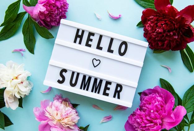 Leuchtkasten mit hello summer text und pfingstrosenblüten auf pastellblauer oberfläche