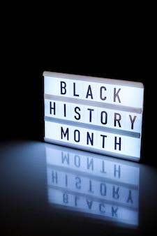 Leuchtkasten mit text black history month auf dunkelschwarzem hintergrund mit spiegelreflexion. historisches ereignis melden. hell