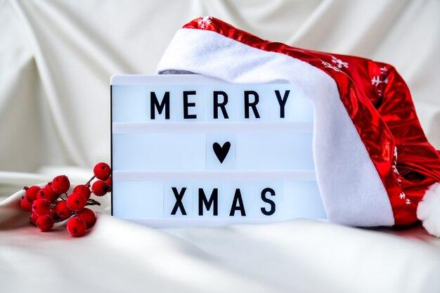 Leuchtkasten mit text frohe weihnachten mit weihnachtsmütze auf seidenstoff hintergrund winterurlaub konzept
