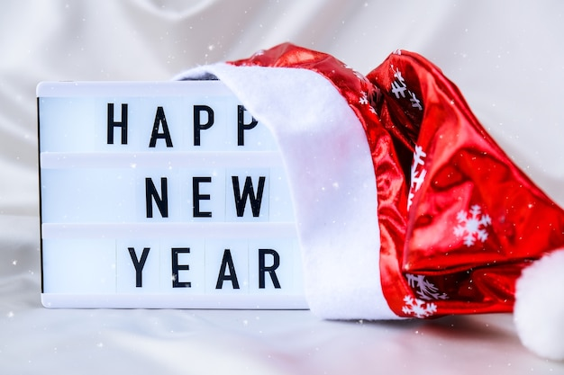 Leuchtkasten mit text frohes neues jahr mit weihnachtsmütze auf seidenstoffhintergrundwinterurlaubskonzept